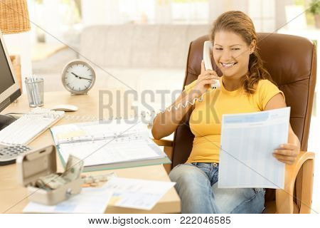Home finances. Happy young woman calculating private expenses at home, using calculator, calculating family budget.