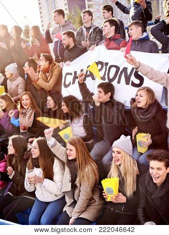 Fans cheering in stadium and eating popcorn in yellow boxes and drink beer. Group young people friends support your favorite team. Close up. School competitions.