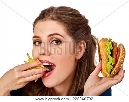 Woman eating french fries and hamburger. Portrait of student consume fast food on table. Victory over dyslexia. Girl trying to eat junk. Good appetite and metabolism