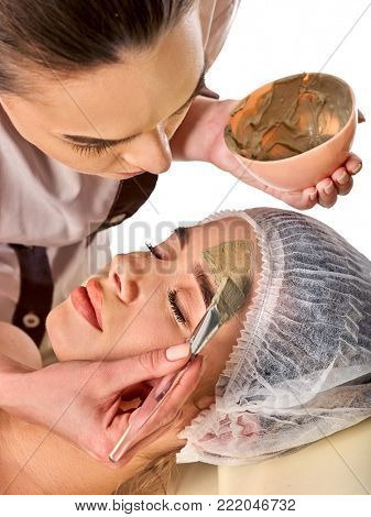 Mud facial mask of woman in spa salon. Massage with clay full face. Girl on with therapy room. Beautician with bowl therapeutic procedure isolated background.