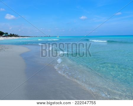 Sandy beach at Caribbean Sea in VARADERO city in CUBA with fresh water on seaside landscape and exotic palms and trees, clear blue sky in 2017 warm sunny spring day, North America on March.