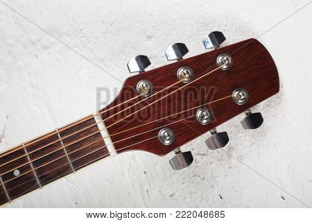 Musical instrument - Neck acoustic guitar on a white brick wall background.