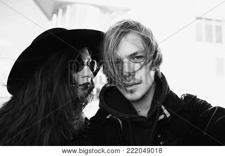 Selfie photo of man and woman with curly hair in coat. Black and white art monochrome photography. Black and white creative photography. Black and white conceptual image. Beautiful black and white background. Black and white portrait.
