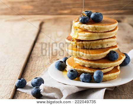Pancakes day background, stack of homemade pancakes with blueberries over wooden table, rustic