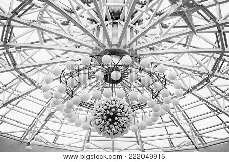 Big beautiful chandelier on the ceiling. Black and white art monochrome photography. Black and white creative photography. Black and white conceptual image. Beautiful black and white background.