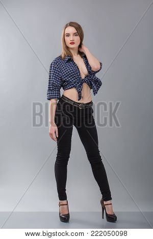 stylish girl in a cowboy shirt without a bra on a grey background. Cowboy style. model tests