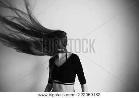 Girl with very long hair to the waist on a white background. Black and white art monochrome photography. Black and white creative photography. Black and white conceptual image. Beautiful black and white background.