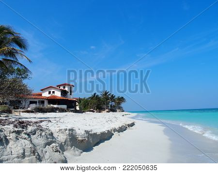 Home at sandy beach at Caribbean Sea in VARADERO city in CUBA with clear water on seaside landscape and exotic palms and trees, clear blue sky in 2017 warm sunny spring day, North America on March.
