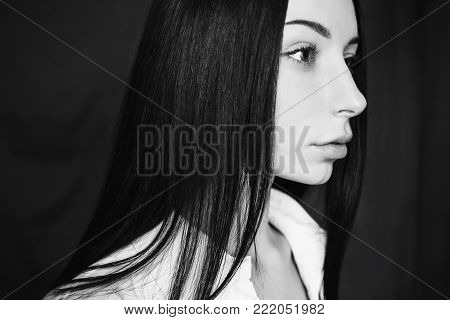 Black and white art monochrome photography. Black and white creative photography. Black and white conceptual image. Beautiful black and white background. Black and white portrait. Emotional portrait of brunette girl with long straight black hair