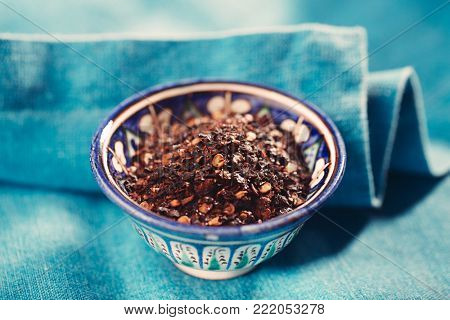 chipotle jalapeno smoked chili flakes in bowl on textured blue background