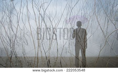 The man stands with a lonely umbrella with dried branches up from the water. The image overlays can be used as a background.
