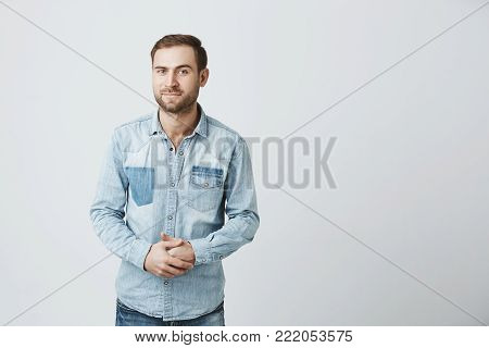 Portrait of puzzled european male wears fashionable denim clothes, keeps hands in together, raises eyebrow in bewilderment, has to make difficult life choice, looks confused