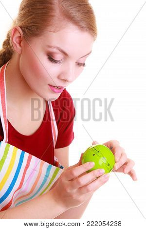 Housewife or chef in colorful kitchen using apple timer eggtimer isolated studio shot