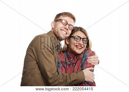 Portrait of joyful cute young European girlfriend and boyfriend wearing similar stylish oval shaped glasses cuddling, their broad smiles expressing happiness and joy. So happy to be together