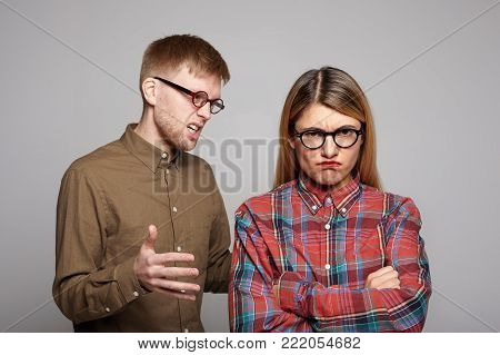 Studio shot of you European couple having argument: bearded guy in oval glasses trying to convince his stubborn girlfriend who is crossing arms and making displeased grimace, expressing disagreement