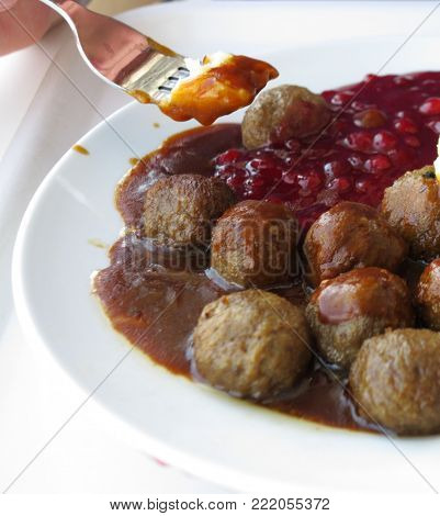 Food being eaten. Swedish meatballs potatoes cranberry on dish. A traditional scandinavian culinary.