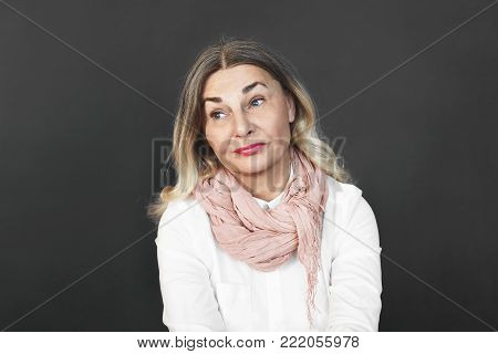 Portrait of attractive middle aged woman with colored loose hair and blue eyes having bored look while spending evening all alone. Negative human emotions, sadness, boredom or disappointment