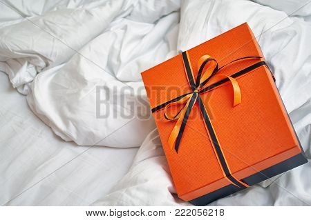 A fashionable black box with an orange lid for a gift tied with a black and orange ribbon with a beautiful bow lies on the bed.