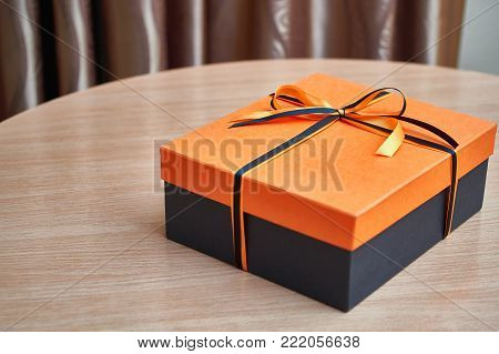 An elegant black box with an orange lid for a gift tied with a black and orange ribbon with a beautiful bow.