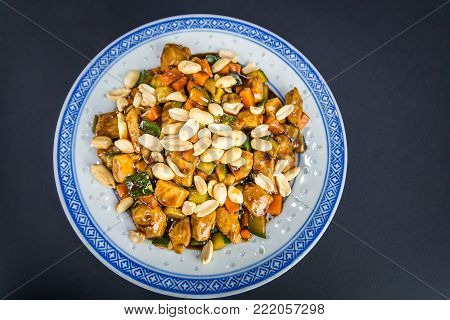 Chinese food. Spicy Kung Pao Chicken with peanuts, cucumber and carrot, traditional Chinese Dish on black background.