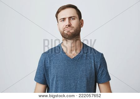 European hesitant bearded man frowns face, thinks over future plans, being little puzzled, poses against gray background. Caucasian male confused and dissatisfied with unexpected news
