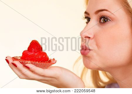 Sweets, junk food, sugar temptation on diet concept. Woman holding sweet delicious cupcake sending air kisses to dessert.