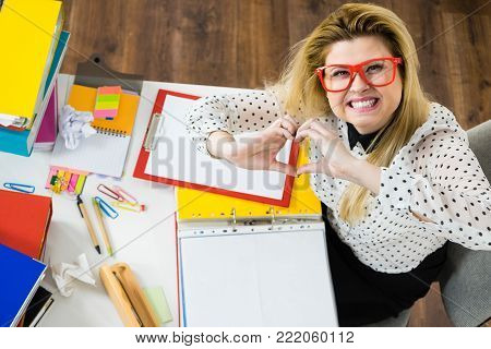 Happy business woman feeling energetic sitting working at desk full off documents in binders showing heart gesture with hands