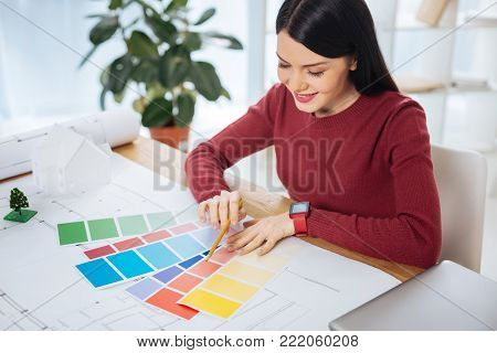 Favorite palettes. Experienced creative talented designer feeling glad while sitting at the table and looking at the beautiful bright color palettes and smiling