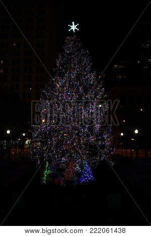 Big Beautiful Multicolored Christmas Tree with Red, Green and Blue lights and a Star on top in Millennium Park, Chicago with a dark background due to a small aperture effect, December 5th, 2017