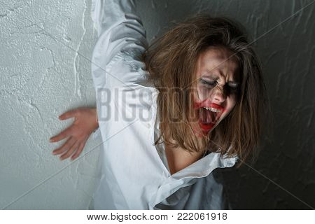 crazy woman with fluffy hair near wall screaming