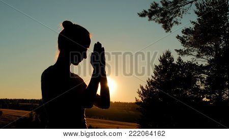 Silhouette of young woman praying in forest at sunset. Sunset light, sun lens flares, golden hour. Religion, spiritual and nature concept