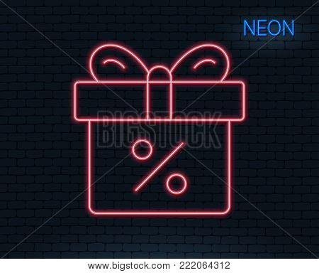 Neon light. Gift box with Percentage line icon. Present or Sale sign. Birthday Shopping symbol. Package in Gift Wrap. Glowing graphic design. Brick wall. Vector