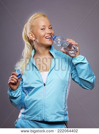 Image of sportwoman with bottle of water