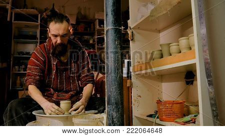 Professional male potter working with clay on potter's wheel in workshop, studio. Handmade, art and handicraft concept