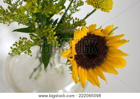 The focal point of this flower arrangement is the bright yellow sunflower with dark brown center.