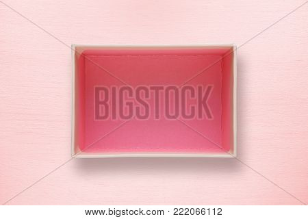 Opened box top view on pink background
