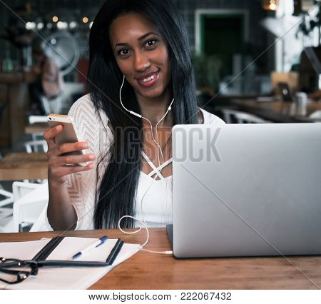 portrait of happy young african woman in a coffee shop using mob