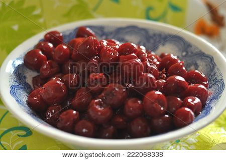 A bowl with pitted cherries, cooking process. Top view.
