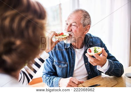 Senior couple eating breakfast at home. An old man and woman sitting at the table, eating breakfast.