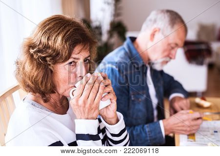 Senior couple relaxing at home. An old man and woman sitting at the table, drinking coffee and doing crosswords.