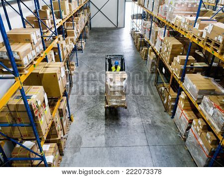 Man forklift driver working in a warehouse. High angle view.