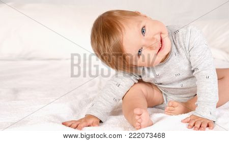 Baby Girl In White Bedding At Home