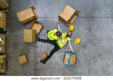 An accident in a warehouse. Man lying on the floor among boxes, unconscious. A woman helping her colleague. Top view.