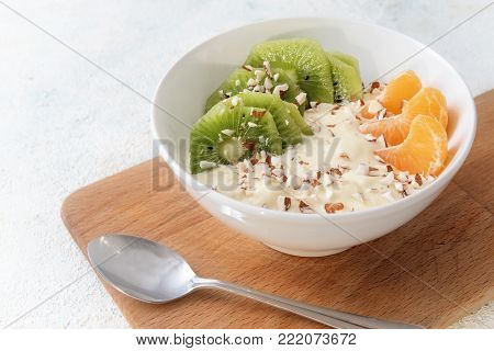 healthy breakfast with protein from quark or curd cheese, linseed oil with omega 3 fatty acids, fresh fruits and nuts, budwig diet in a white bowl on a wooden kitchen board and a light background with copy space, selected focus