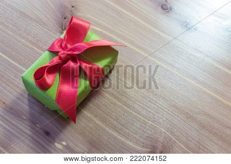 Small gift, diagonal on a wood table, wrapped in green with big red satin bow, copy space, horizontal aspect
