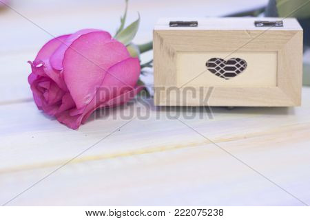 The concept of Love, Wedding, Proposal, Anniversary, St. Valentine's Day, Mother's Day with a beautiful pink rose and decorative wooden casket in a close up, light wooden background