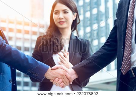 Successful Business concept, Business people handshaking behind woman smiling background after good deal with partnership signed agreement, Business meeting and agreement concept.