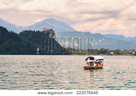 Bled, Slovenia - July 05, 2017: Tourists sailing across the lake Bled on wooden flat-bottom Pletna boat.