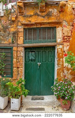 Old Wall With Green Locked Door And Flowers