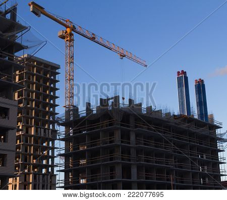 Construction site the construction of a multistory building, the installation of the metal panels crane in yellow on a background of blue sky. Concept construction